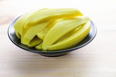 Preserved mango fruits in black bowl Stock Photo