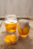 Preserved peach compote with whole peaches in glass jars Royalty Free Stock Photography