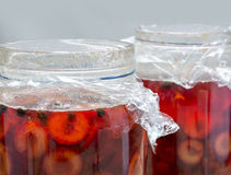 Preserved red fruits with spices into two glass jars stock photos