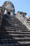 Preserved 12th century Angkor Wat temple steep staircase. Scene around the Angkor Archaeological Park. The site contains the remains of the different capitals of Royalty Free Stock Photos