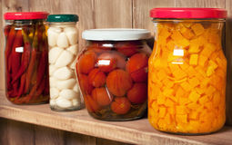 Preserved  vegetable on shelf near a brown wall Royalty Free Stock Photo