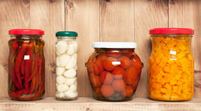 Preserved  vegetable on shelf near a brown wooden. Wall Royalty Free Stock Images