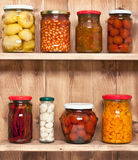 Preserved  vegetable on shelf near a wooden wall Stock Photos