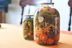 Preserved vegetables in glass jars on the home kitchen table royalty free stock images