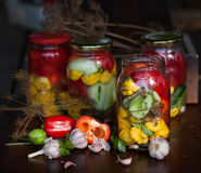 Preserved wegetables in jars. Preserved cucumbers, peppers and patisson in jars Royalty Free Stock Images