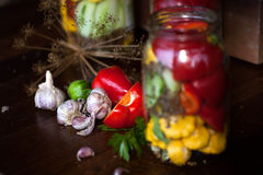 Preserved wegetables in jars. Preserved cucumbers, peppers and patisson in jars Royalty Free Stock Photo