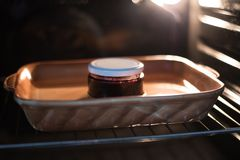 Preserving jam in oven. Preserving jar of jam in oven Royalty Free Stock Photos