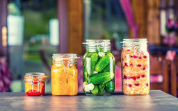 Preserving. Pickles jars. Jars with pickles, pumpkin dip, white cabbage, roasted red yellow pepper. Pickled Vegetables. Stock Photos