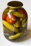 Preserving. Preparations for the winter. Pickles and tomatoes in a glass jar. Closed with an iron lid. Autumn royalty free stock photos