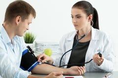 Presión arterial de medición del doctor de sexo femenino de la medicina al paciente foto de archivo