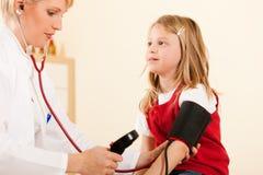 Presión arterial de medición del doctor del niño Imágenes de archivo libres de regalías