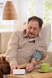 Presión arterial de medición del viejo hombre en casa Imagenes de archivo