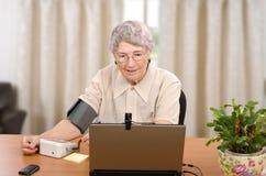 Presión arterial de medición delante del monitor de computadora Imagen de archivo