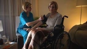 Presión arterial de medición de la mujer de la enfermera de sexo femenino, hipertensión, desesperación de la edad avanzada almacen de metraje de vídeo