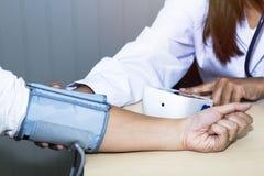 Presión arterial del control profesional del doctor de la mujer de la mano con el paciente Fotos de archivo