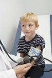Presión arterial del doctor Checking Boy fotografía de archivo