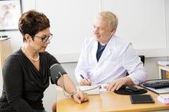 Presión arterial del doctor Checking Female Patient foto de archivo libre de regalías