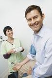 Presión arterial del doctor Checking Patient Imagen de archivo libre de regalías