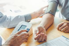 Presión arterial arterial del doctor Measuring con el paciente del hombre en atención sanitaria del brazo en hospital imagen de archivo libre de regalías