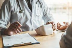 Presión arterial arterial del doctor Measuring con el paciente del hombre en atención sanitaria del brazo en hospital fotografía de archivo