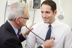 Presión arterial del doctor Taking Male Patient en hospital Imagen de archivo