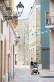 Presicce, Apulien - eine Frau, die ihren Spaziergänger durch das alte dreht lizenzfreies stockbild