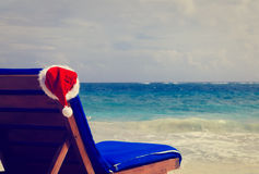 Presida a sala de estar com o chapéu vermelho de Santa na praia Imagem de Stock Royalty Free