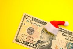 Free President Hamilton In A Red Santa Claus Hat On A Ten US Dollar Bill Against A Bright Yellow Background. The Concept Of The Cost Of Royalty Free Stock Photos - 132150788