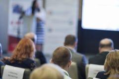 Presidente del anfitrión que se coloca en etapa delante de la audiencia en la conferencia Fotografía de archivo libre de regalías