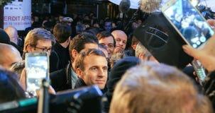 Presidente francés Emmanuel Macron en el mercado de la Navidad con la muchedumbre fotos de archivo