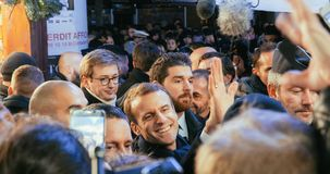 Presidente francês Emmanuel Macron no mercado do Natal com multidão imagem de stock