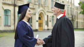 Presidente que dá o diploma ao estudante fêmea, agitando a mão, convocação vídeos de arquivo