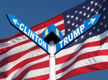 Presidential elections in the US. Names of Clinton and Trump written in a directional road signs against american flag Royalty Free Stock Photos