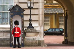 Presidential limousine and guard Buckingham Palace. Guard on sentry duty outside Buckingham Palace, with the US Presidential limousine in the background - during Royalty Free Stock Image