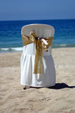 Presidenza bianca con il nastro dell'oro per una cerimonia nuziale di spiaggia Fotografia Stock