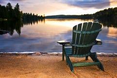 Presidenza di legno al tramonto sulla spiaggia Fotografie Stock Libere da Diritti