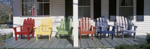 Presidenze di legno colorate sul portico fotografie stock libere da diritti