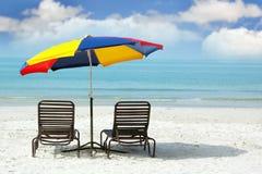 Presidenze di legno ed ombrello variopinto sulla spiaggia Fotografia Stock Libera da Diritti