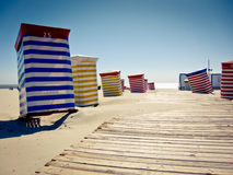 Presidenze di spiaggia variopinte sulla sabbia piena di sole immagine stock