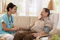 Presión arterial de medición de la enfermera Imagen de archivo libre de regalías