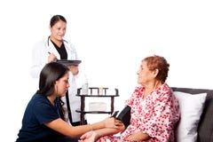 Presión arterial de medición de la enfermera Imagen de archivo