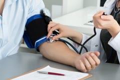 Presión arterial de medición del doctor de sexo femenino de la medicina al paciente Imagen de archivo libre de regalías