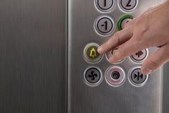 Presionado a mano el botón de la alarma en el elevador Imágenes de archivo libres de regalías