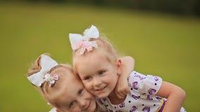 Presionan a dos pequeñas hermanas gemelas cara a cara, divirtiéndose en un prado verde en verano Abrazo de caída en almacen de video