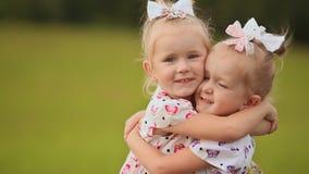 Presionan a dos pequeñas hermanas gemelas cara a cara, divirtiéndose en un prado verde en verano Abrazo de caída en metrajes