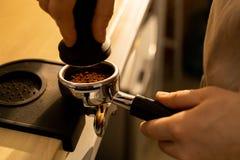 Presionar el café molido en portafilter imagenes de archivo