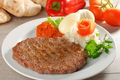 Presliced traditional burger patty called pljeskavica. Served with pita bread with some cream cheese Kajmak. Balkan food Royalty Free Stock Photography