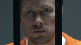 Preso desesperado con las cicatrices en la cara que mira a través de barras de la célula, encarcelamiento almacen de metraje de vídeo