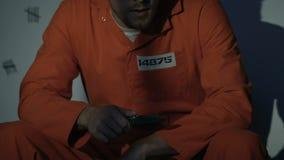 Preso masculino caucásico que se sienta con el cuchillo en la célula, escape del planeamiento, libertad almacen de metraje de vídeo