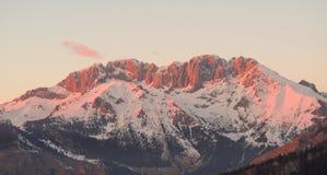 Presolana是Orobie的山脉,意大利阿尔卑斯 背景捷克最高的横向山snezka冬天 在日落岩石成为红色,桔子和桃红色 免版税库存照片